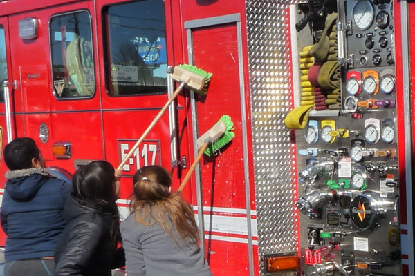 Taylorsville fifth-graders help wash down fire trucks before they enter the new station. (Carl Fauver/City Journals)