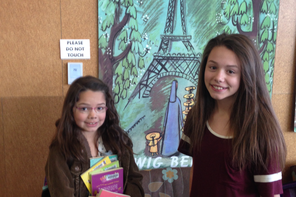 Mira, Ella and Matthew Barnett pose with a movie schedule. They attended all the French movie screenings held at the Viridian from January to April. (Nicole Barnett)