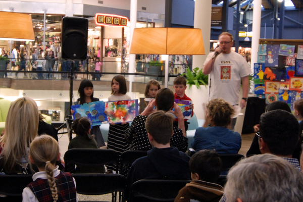 Winners at the first-grade level presenting their art work to the audience. (Keyra Kristoffersen/City Journals)