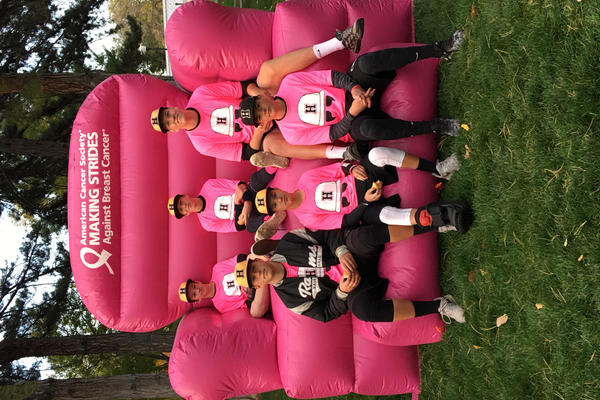 Highland players pose on a bright pink chair at their Making Strides Against Breast Cancer fundraiser. Pink is the universal color for breast cancer awareness.