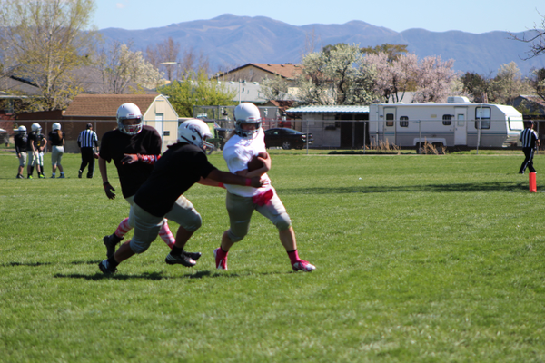 Kammie Bilanzich [insert name] tries to elude a would-be tackler. The team plays every Saturday through May at Westmore Elementary in West Jordan. (Travis Barton/City Journals)