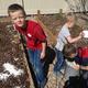 Eric, Enoch and Elijah Oler scatter smashed eggshells onto their garden beds. (Natalie Conforto/City Journals)