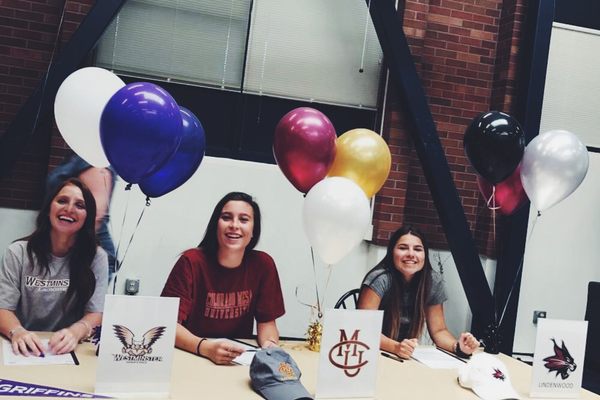 Left to right: Kennedy Flavin, Nici Boutwell and Katie McRoberts smile after signing their letters of intent to their chosen colleges. (Mike Flavin)