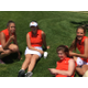 Some Brighton girls tennis players hang out on the grass in their Tiger uniforms. (Clark Garso/ Brighton High School)