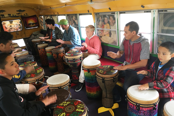 "Nels Anderson, wearing the green hat, teaches community members how to play djembe drums. Anderson brought his ""mobile music room"" DrumBus to the Kearns Library on April 24. (Tori La Rue/City Journals)"