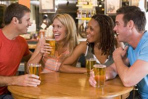 Medium group of young friends drinking and laughing in a bar