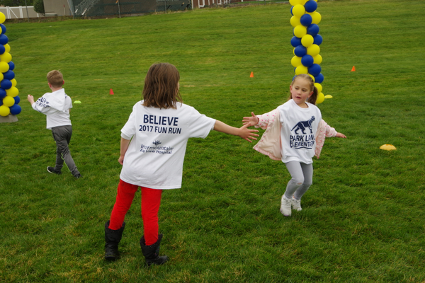 A Park Lane student encourages another during the school's fun run fundraiser. (Julie Slama/City Journals)