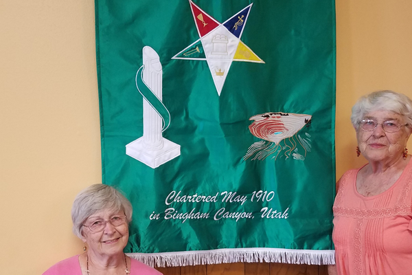 Betsy Jones and Nancy Strader show the Martha chapter banner in their Eastern Star meeting room. (Ruth Hendricks/City Journals)