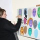 Liz Bunker, an art teacher, ran the self-portrait activity where people could draw or paint themselves onto one of 59 faces. The faces were all painted onto two separate doors. (Travis Barton/City Journals)