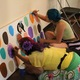 People used paint markers to draw self-portraits onto one of 59 faces during the Night on Commonwealth event in May. (Travis Barton/City Journals)