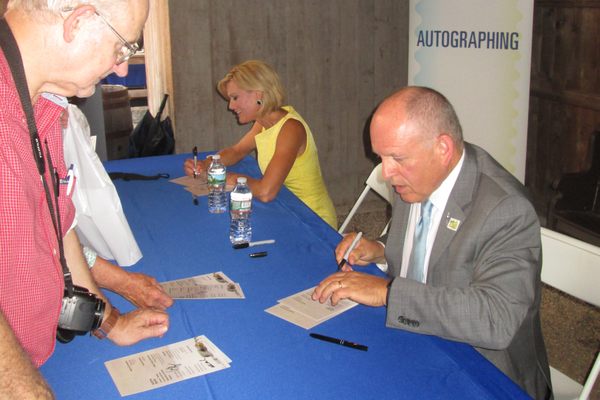Newscaster Cecily Tynan and Patrick Mendonca of the U.S. Postal Service signed cards documenting the day of issue for the Wyeth stamps.