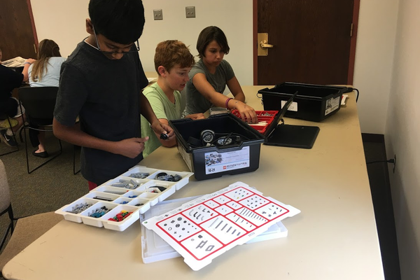 A group use pictorial instructions and a Lego EV3 to figure out how to design a robotic arm. (Kelly Cannon/City Journals)