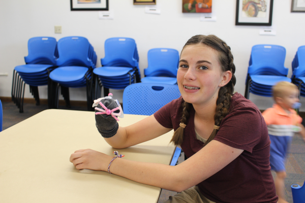 Laurel Dalton shows off her sock puppet after she completed hers at the Tyler Library (Travis Barton/City Journals)