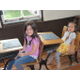 Madi and Olivia Martin get a taste of what sitting in class was like a century ago. (Carl Fauver/City Journals)