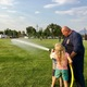 Taylor Langstrom of Salt Lake Unified Fire Authority shows kids how to spray a fireman's hose. (Lexi Peery/City Journals)