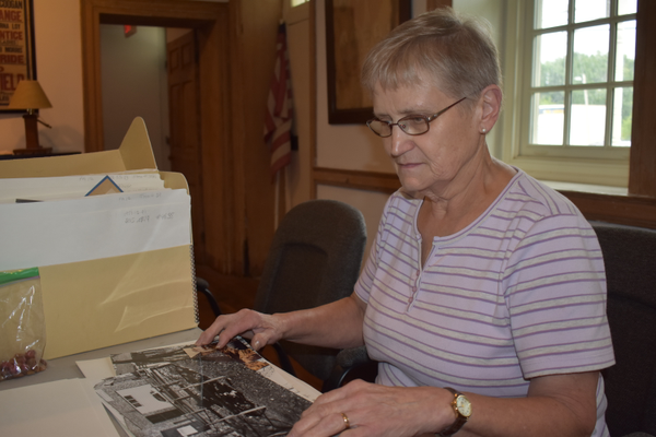 Carol Grigson of the Downingtown Area Historical Society goes through some photos of the Log House. The society was the driving force behind the major renovation and relocation of the house. (Photo by Natalie Smith)
