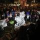 An ice sculpture draws a crowd on Third Street South.