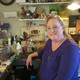 Artist Deb Mackie at her workbench where she crafts tiny leather purses and saddles dolls and dioramas