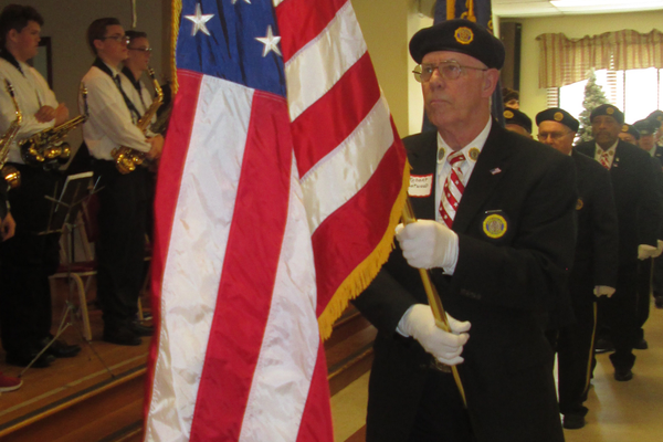 The flag is presented by members of American Legion Post 491.