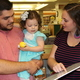 """Aubrae Pope (right) shows her daughter Hazel, 2, the scholarship check she received after winning the """"Book Your Summer"""" drawing. Hazel's father, Ken, holds her up for a better view. (Sharon Deeds/Utah State Library)"""