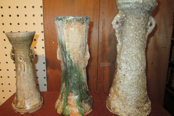 The vases and serving pieces by Gill Mallinckrodt have rough, ancient-looking surfaces.