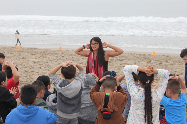 Staff member Brittany Olaes teaches a class on the beach