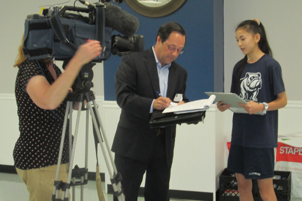 A TV news crew interviews a St. Cornelius student after the assembly.
