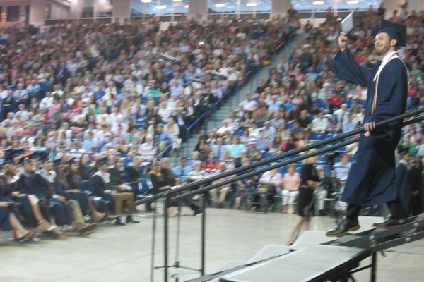 A new graduate waves to the crowd.