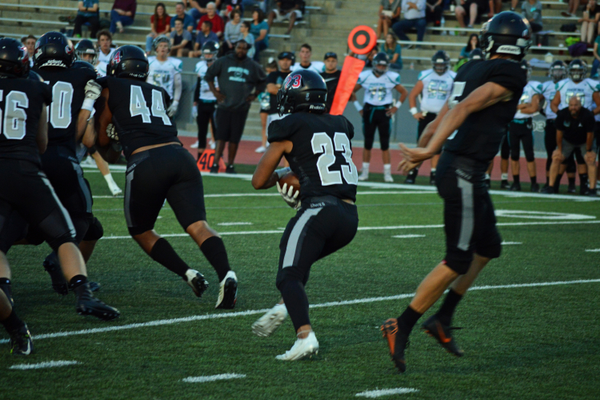 Cinco Lucero hands the ball off to Dallin Pan.