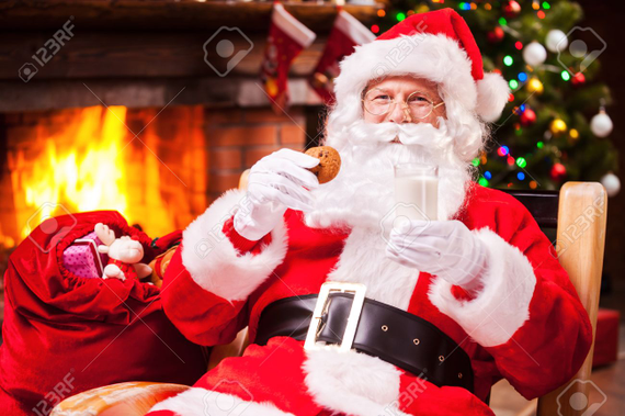 33572381 my favorite meal cheerful santa claus holding glass with milk and cookie while sitting at his chair