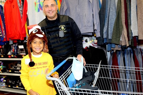 Deputy Brian Bolt and student Titus search for Christmas gifts at Walmart on Saturday.