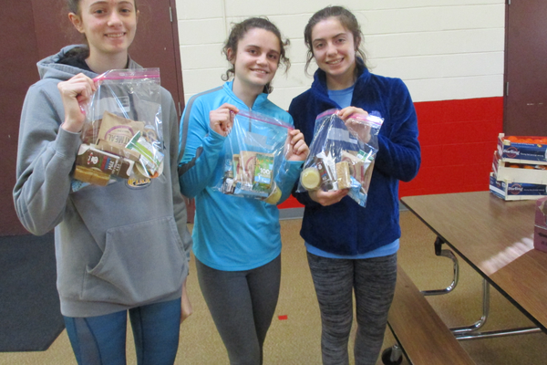 Unionville High School volunteers with a few of the completed meal kits at Hillendale.