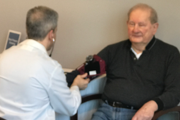 Dr. John Ragucci takes the blood pressure of a visitor to the open house at the Circle Health Tewksbury medical facility.