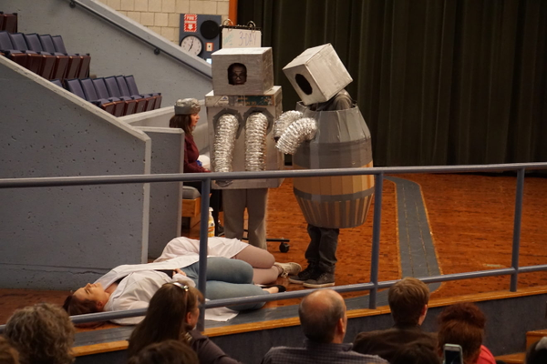 "Senior Brooklyn Savard looks up as robots approach her in Greater Lowell Tech's production of ""10 Ways to Survive the End of the World."" (Courtesy Photo Greater Lowell Tech)"