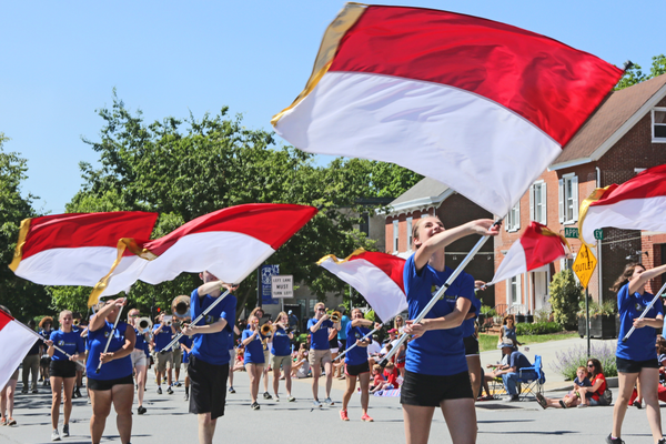 The Unionville High School Band Front waves red and white banners.
