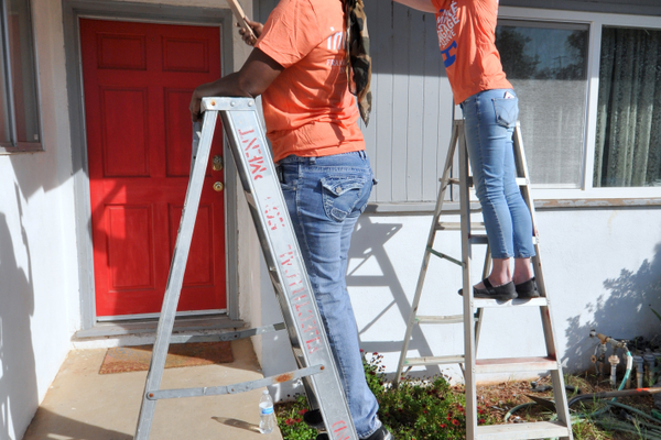 Volunteers prepare the home's exterior for a new paint job.