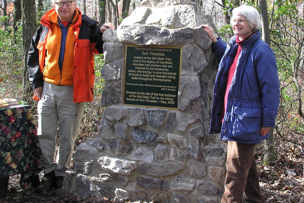 Tom and Barbara Thwaites at the Tom Thwaites Memorial, dedicated in 2003 near Little Flat tower, where clearing for the trail began in 1969. Thwaites, who authored the Mid State Trail Guide and the 50 Hikes series of books, passed away Christmas Day, 2014. Photo by Ralph Seeley
