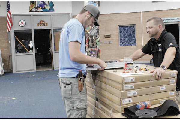 Alcom's Noah Eaker, a CHS grad, talks with CHS Principal Kevin Doran about one of the LED lighting components that will brighten up the CHS Library. (photos by MEP/The Eagle)