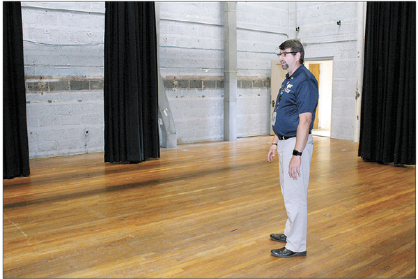 THE STAGE BEFORE – Principal Todd Dellinger shows what the Starnes Auditorium stage floor looked like prior to its refinishing work being completed.