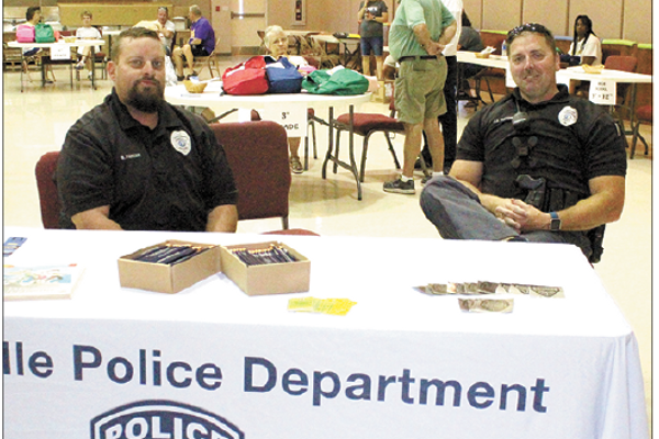 Cherryville Police Department personnel Lt. Brandon Parker (left) and Patrol Officer Jason Parton handed out Junior Police Officer badges and pencils as well as safety advice at the back pack and school supplied event last Saturday.