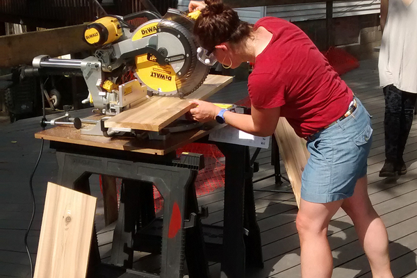 A workshop participant using a compound miter saw.