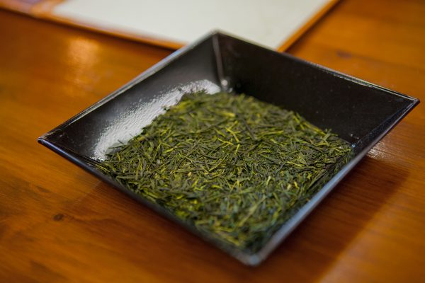 Green tea leaves in black dish
