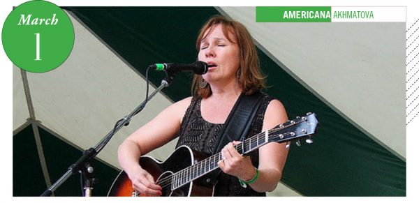 Iris DeMent singing onstage with guitar
