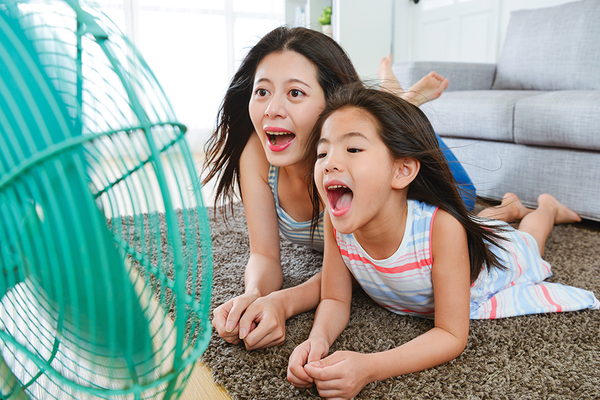 Mother daughter lying in front of fan