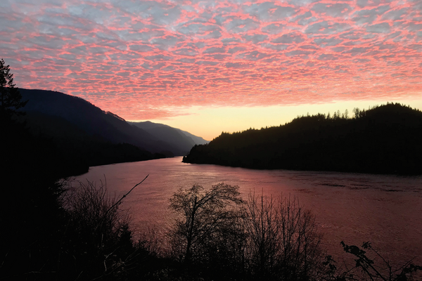 Billowy pink clouds float over a sunset-tinged Columbia River