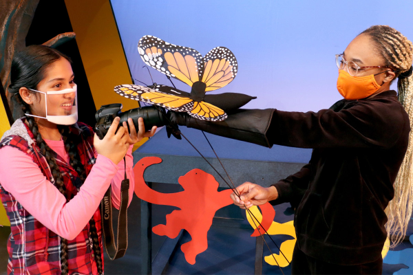 two young actresses onstage, fake butterfly