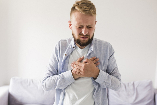 Man holding chest from experiencing heartburn symptoms of gastroesophageal reflux