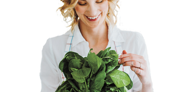 Woman holding bundle of leafy greens to detox her diet