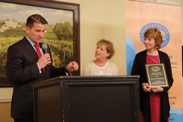 Mayor Tim Brown introduces Denise McDermott, center, this year's Educator of the year.