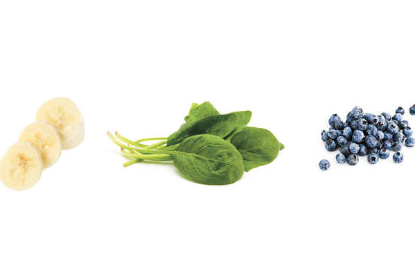 Ingredients for homemade baby food smoothie using sliced banana, spinach, and blueberries